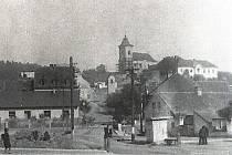Pohled na počapelské náměstíčko s rybníčkem a tyčícím se kostelem na návrší kolem roku 1920.
