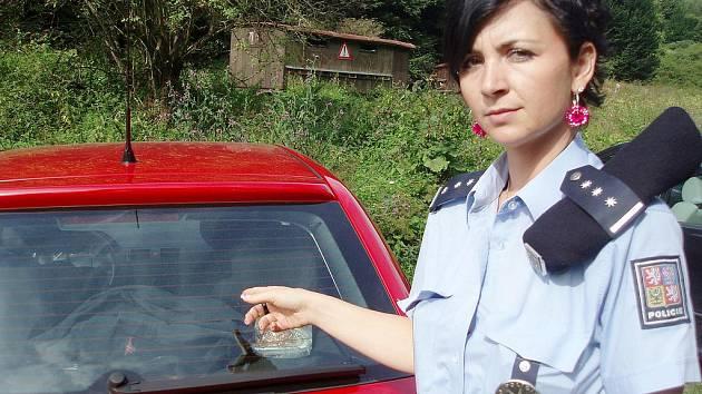 Policistka ukazuje na věci, které majiel vozu nechal uvnitř.