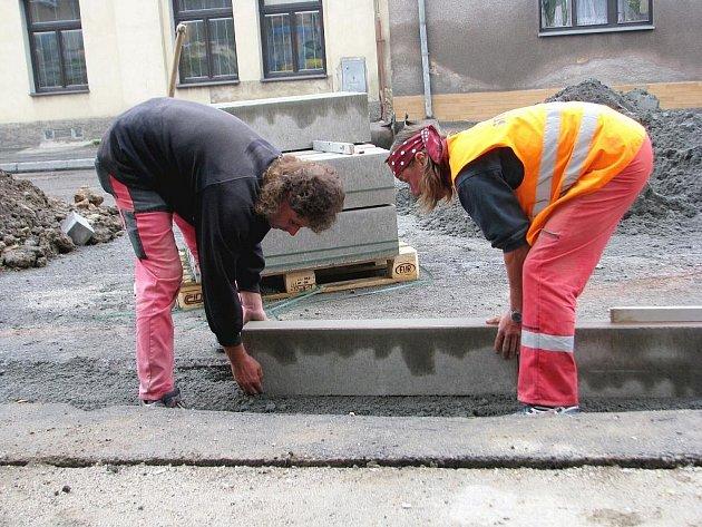 Dělnící pokládají obrubníky, které rozdělí silnici a cyklostezku