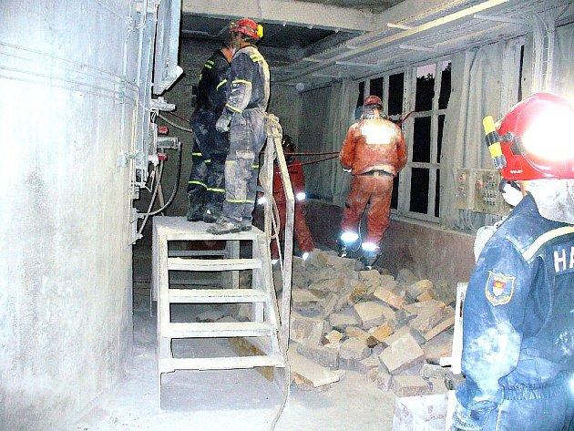 ZÁCHRANNÁ AKCE. Vyproštění zavaleného dělníka ze sutin v šachtové peci trvalo hasičům, záchranářům i místním zaměstnancům Vápenky Čertovy schody ve Tmani přes tři hodiny. Suť bylo nutné odklízet ručně pomocí kbelíků.