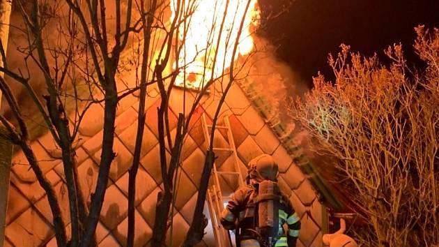 Z požáru chaty v nepřístupném terénu ve Vráži na Berounsku v noci na sobotu 20. února 2021.