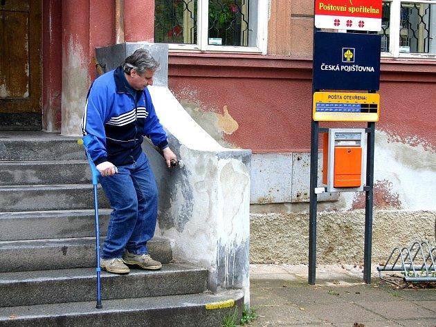 Přístup do budovy České pošty v Komárově ztěžuje zdravotně postiženým zábradlí, které nedosahuje celé délky schodiště