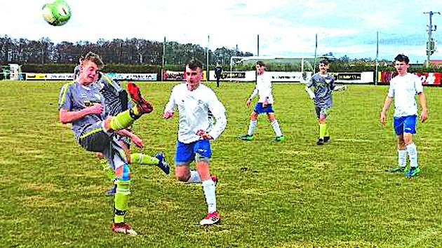 Hostující Martin Vyšín (v bílém) sleduje nepovedený odkop domácího hráče.