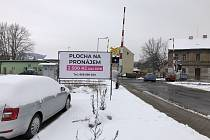 Billboard u železničního přejezdu mezi Brožíkovou a Tylovou ulicí