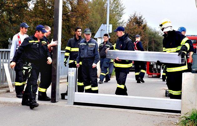 Králodvorští hasiči staví mobilní hráz.