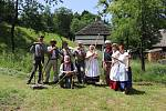 Muzejníci při sečení trávy.