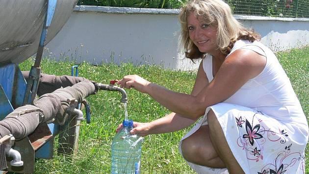 Marie Jíňová čepuje vodu z cisterny na návsi Slaníku