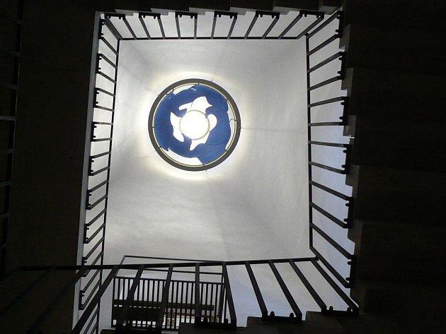 Nad schodištěm vedoucím k Rytířskému sálu je skleněná vitráž zobrazující tři straky držící v zobáku zlatý kruh.