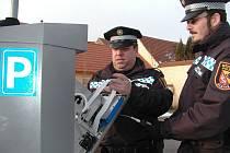 Velitel městských strážníků Petr Vaněk (vlevo) s Janem Šlehoferem při výměně papírové pásky na stvrzenky v  jednom z parkovacích automatů.