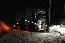 Kamion uvízl na zasněžené silnici.