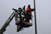 Zaměstnanci technických služeb uklízejí svítící sněhové vločky z ulic města. Další den je čekají ještě stromy.