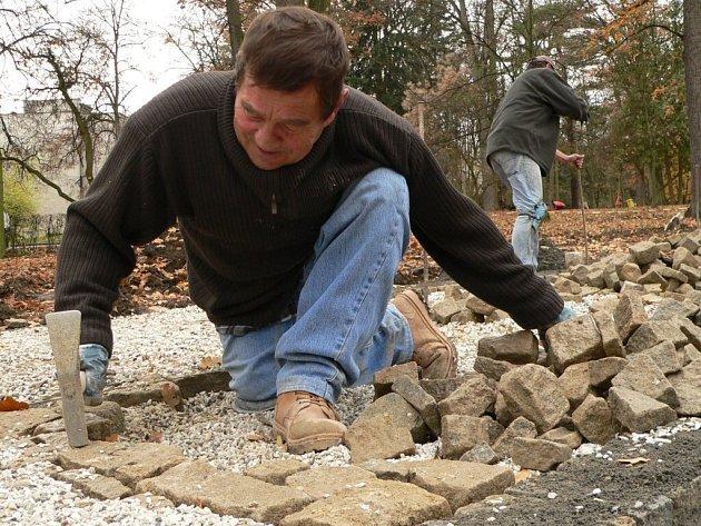 Dělníci pracují na zádlažbě parku.