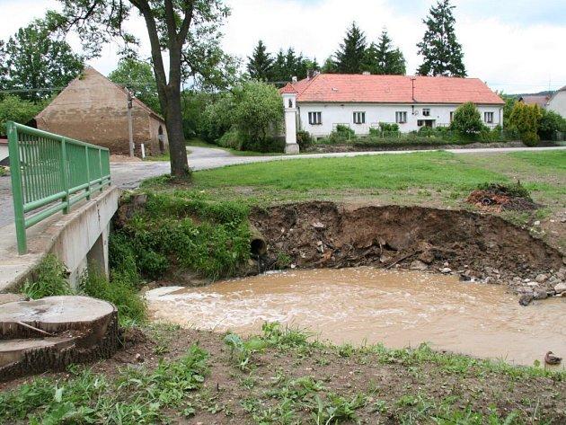 Potok v Bílsku. Z čerstvě nasypané hráze tu úterý 26. května déšť část země splavil.