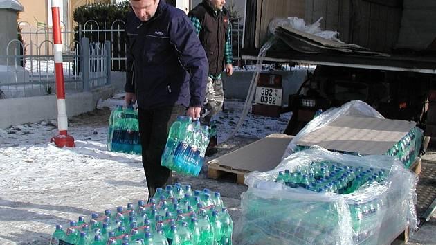 """Na návsi ve Slaníku se v úterý 13. ledna rozdávali pracovníci firmy Karlovarské minerální vody balíky """"matonky""""."""