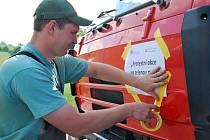 Zemědělec před protestem lepil na náklaďák leták s nápisem Protest za zelenou naftu a tiché víno.