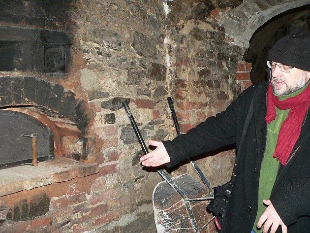 Památkář Ondřej Ševců ukazuje pec v černé kuchyni na strakonickém hradě.