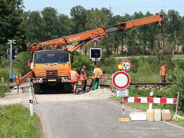 Rekonstrukce železničního přejezdu ve Lhotě u Kestřan.  Vyměňují se poškozené železniční pražce a doplňuje štěrk.