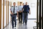 Eskorta vězeňské služby přivádí k soudu obžalovaného čtyřiadvacetiletého Lukáše Nováka. Měl zabít mačetou svého otčíma.