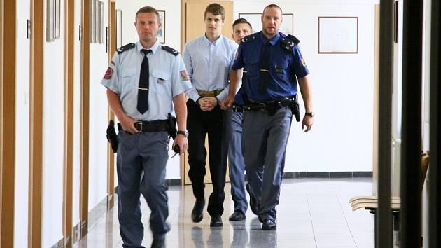 Eskorta vězeňské služby přivádí k soudu obžalovaného čtyřiadvacetiletého Lukáše Nováka.
