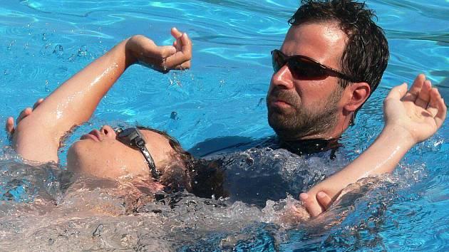 Tělesně postiženým plavcům pomáhají zvládat plavecké dovednosti dobrovolníci i přímo ve vodě.
