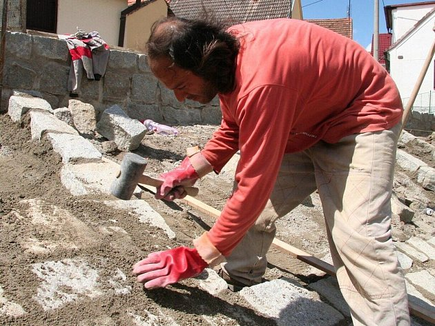 Koryto cehnického potoka dělníci zpevňují dlažbou z lomového kamene.