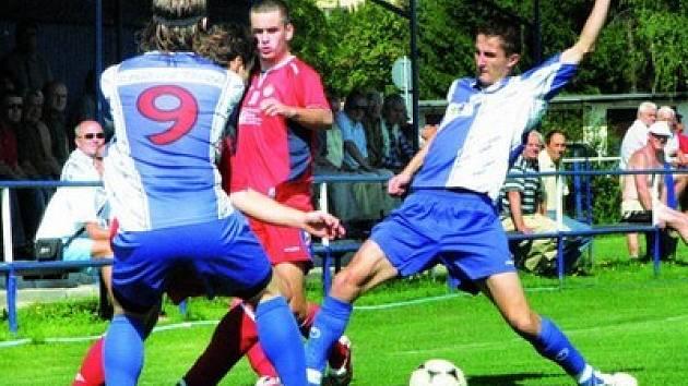Třebonští obránci Procházka (vlevo s č. 9) a Tůma v souboji s klatovskými útočníky. Ve vydařeném utkání Třeboň porazila ambiciózní Klatovy 3:1.
