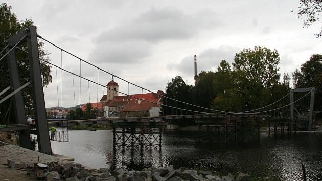 Budování lávky začalo v dubnu. Nejprve se práce odehrávaly na březích. Konstrukce přeťala řeku v srpnu (na snímku). Jedním z posledních kroků byly statické a dynamické zkoušky.