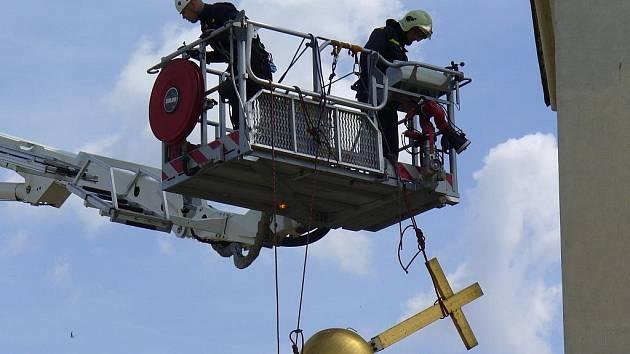 Profesionální hasiči z Mělníka sundávali ulomený kříž z kostela ve Vlíněvsi