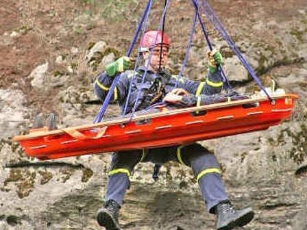 Závěr celé akce. Záchranář spuštěný z vrtulníku si k sobě jistí zraněného ve speciálních nosítkách a nechá se vytáhnout posádkou helioptéry.