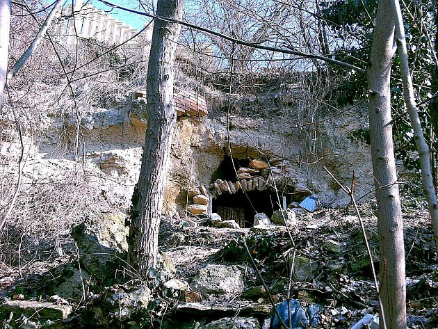 Sklep v pískovcové skále pod mělnickou městskou knihovnou obýval bezdomovec. Uvnitř i všude kolem je spousta odpadků, které tam nanosil za několik měsíců.