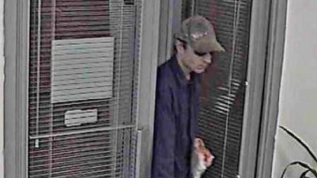 PODOBA.  Záběr průmyslové kamery banky zachytil pachatelovu podobu. Zloděj se maskoval kšiltovkou a slunečními brýlemi.
