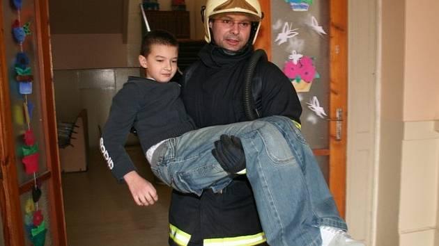"""V NÁRUČI.  Jedno z  dětí, které zůstalo v """"hořící"""" škole, vynesli hasiči v náruči. Druhého museli vynést ven ve vakuové matraci."""