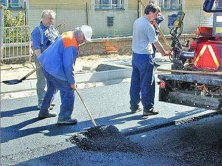 Strojní pokládání asfaltové vrstvy jde rychle a dělníci jen ručně dokončují drobné úpravy.