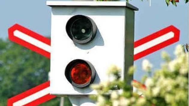Dopravní značení upozorňující na nechráněný železniční přejezd z části zakrývá napevno instalovaný radar. Fotografie byla pořízena přibližně ze vzdálenosti, kde zaznamenává rychlost vozidel, ovšem od kraje silnice.