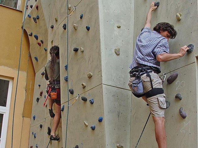 Akční snímek ze závodu dospělých zachycuje soutěžící při zdolávání lezecké stěny v areálu ZŠ Komenského v Kralupech.