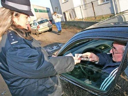 Policistka předává řidiči DVD s  instruktážním filmem
