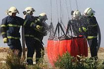 Profesionální a dobrovolní hasiči z Mělnicka v úterý na střemském letišti cvičili naplňování leteckého vodníko vaku