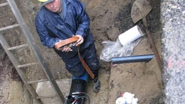 Dělníci ve výkopech v Bezručově ulici usazují nové  vodovodní potrub do stávajících trubek.  Je to metoda reliningu.