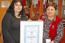 Ředitelka Farní charity Neratovice Miloslava Machovcová (vpravo) a vedoucí sociálních služeb Hana Jarská představují Národní cenu kvality 2012.