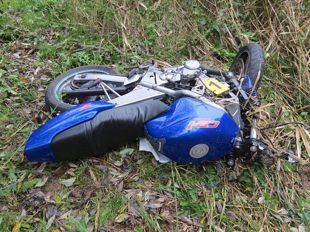 Náraz vyhodil motorku na trávu vedle silnice.