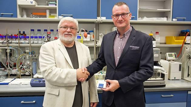 Kralupská společnost Santiago chemikálie vyvinula vlastní technologii přípravy preparátu Remdesivir. Sto balení Aviromixu si převzal ředitel výzkumného centra BIOCEV Pavel Martásek (vlevo).