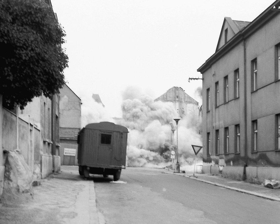 Rohový obytný dům na rohu ulic Fibichova a 28. října byl právě zdemolován řízeným odstřelem. Byla to ohlušující rána a obrovský oblak prachu a kouře se vznesl nad náměstím. Dům se sesul během vteřiny, ale ne úplně. Další domy byly demolovány odstřelem pod