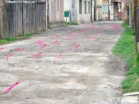 TANKODROM. Červené praporky jasně dokazují, že na pětačtyřicet metrů dlouhé části Máchovy ulice na Blatech je osmdesát hlubokých děr.