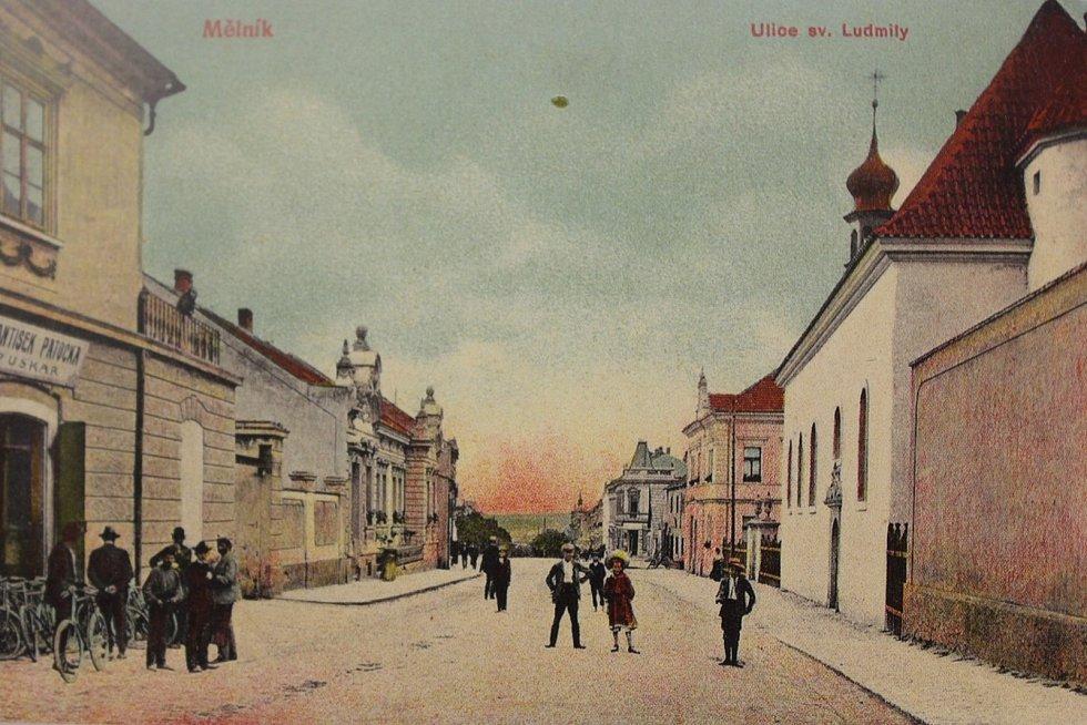 Pohled do dnešní Pražské ulice směrem od nám. Karla IV. Vpravo je vidět opravený kostel sv. Ludmily po kompletní rekonstrukci z let 1906 - 1907 (pohlednice je z roku 1909). Většina levé strany ulice byla zbourána kvůli výstavbě obchodního domu.