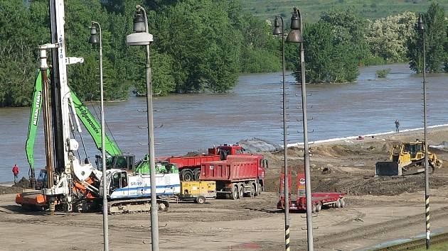 Když začala prosakovat protipovodňová hráz, těžká technika a hasiči pracovali na jejím zajištění.