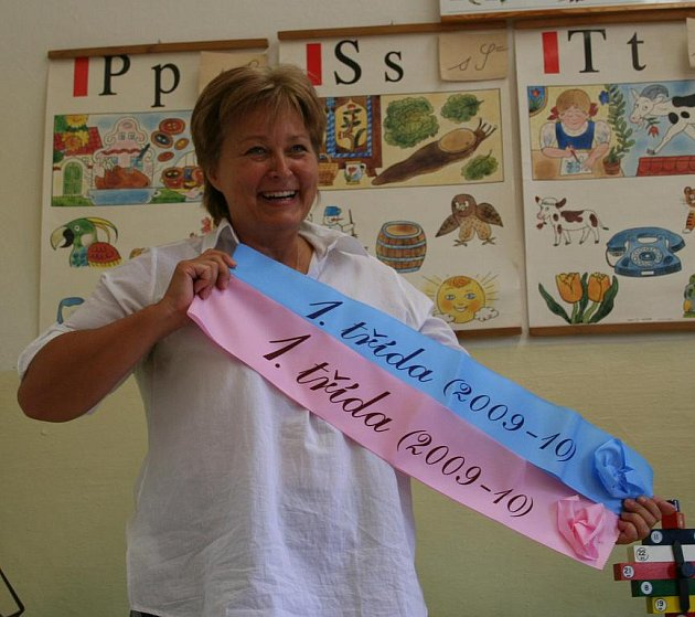 """ŘEDITELKA Základní školy v Želízích Zuzana Paprčková ukazuje barevné šerpy, které si všech šest prvňáčků  odnese jako památku na první školní den. """"Tři růžové jsou připravené pro dívky, tři modré pro chlapce,"""" vysvětlila ředitelka."""