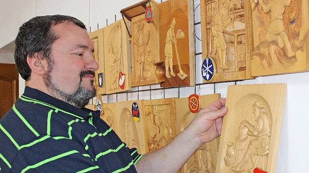 Ředitel kralupského muzea Jan Racek, s dřevěnými reliéfy Vladimíra Cejnara.