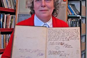 Knihovnice Jitka Lísková s knihou přání, která dokládá vznik místní čtenářské  besedy. Úvodní zápis pochází z ledna roku 1881.