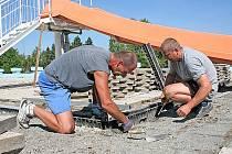 Obsluha mělnického koupaliště vyzvedává dlažbu, která si každoročně o kousek sedne.