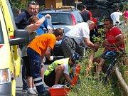 Pořadatelé a záchranáři ošetřují favoritku odpadnuvší těsně před cílem.